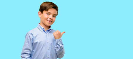 Handsome toddler child with green eyes pointing away side with finger over blue background