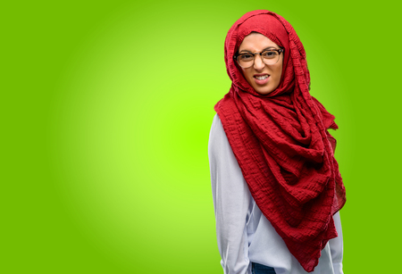 Young arab woman wearing hijab angry and stressful frowns face in dissatisfaction, irritated and annoyed, expressing anger