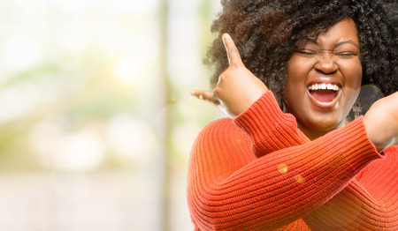 Beautiful african woman making rock symbol with hands, shouting and celebrating, outdoor