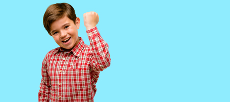 Handsome toddler child with green eyes happy and excited expressing winning gesture. Successful and celebrating victory, triumphant over blue background Stock Photo