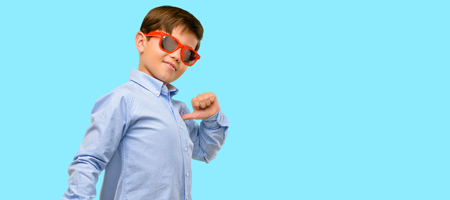 Handsome toddler child with green eyes proud, excited and arrogant, pointing with victory face over blue background Stock Photo