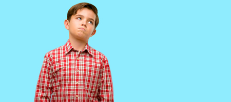 Handsome toddler child with green eyes doubt expression, confuse and wonder concept, uncertain future over blue background Stock Photo