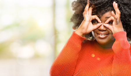 Beautiful african woman looking at camera through her fingers in ok gesture. Imitating binoculars, outdoor