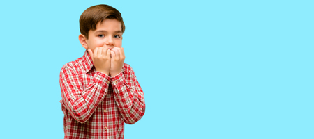 Handsome toddler child with green eyes terrified and nervous expressing anxiety and panic gesture, overwhelmed over blue background