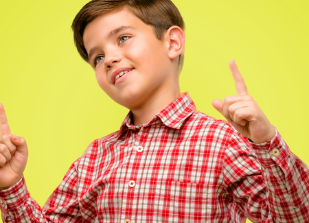 Handsome toddler child with green eyes happy and surprised cheering pointing up over yellow background Stock Photo