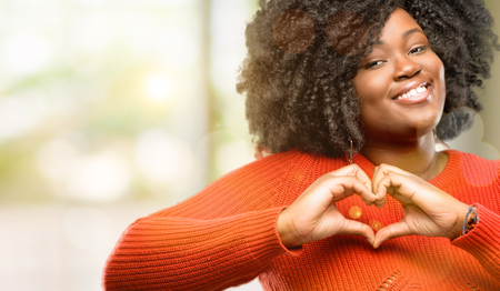 Beautiful african woman happy showing love with hands in heart shape expressing healthy and marriage symbol, outdoor 免版税图像