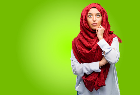 Young arab woman wearing hijab thinking and looking up expressing doubt and wonder Stock Photo