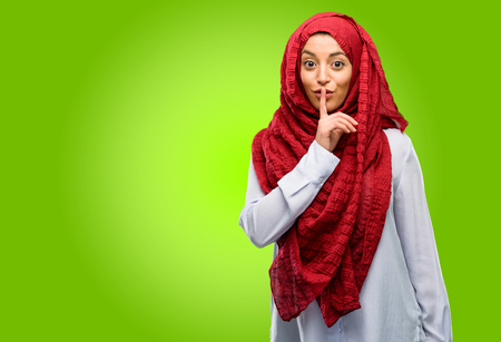 Young arab woman wearing hijab with index finger on lips, ask to be quiet. Silence and secret concept