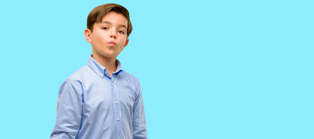 Handsome toddler child with green eyes expressing love, blows kiss at camera, flirting over blue background