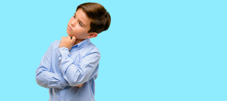 Handsome toddler child with green eyes thinking and looking up expressing doubt and wonder over blue background Stock Photo