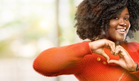 Schöne afrikanische Frau, die glücklich zeigt, Liebe mit Händen in der Herzform zu zeigen, die gesundes und Ehe-Symbol ausdrückt, im Freien