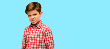 Handsome toddler child with green eyes angry and stressful frowns face in dissatisfaction, irritated and annoyed, expressing anger over blue background