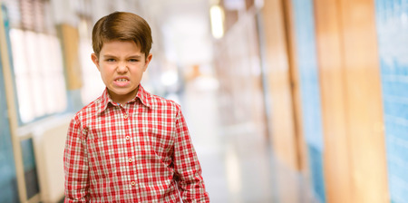 Handsome toddler child with green eyes angry and stressful frowns face in dissatisfaction, irritated and annoyed, expressing anger at school corridor