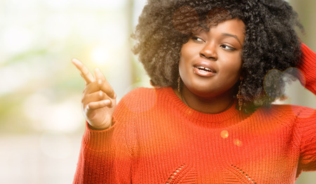 Beautiful african woman pointing away side with his finger, outdoor