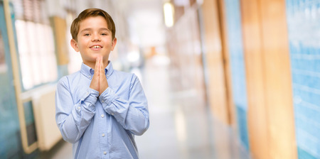 Handsome toddler child with green eyes with hands together in praying gesture, expressing hope and please concept at school corridor