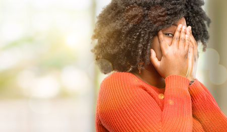 Beautiful african woman smiling having shy look peeking through her fingers, covering face with hands looking confusedly broadly, outdoor Stock Photo