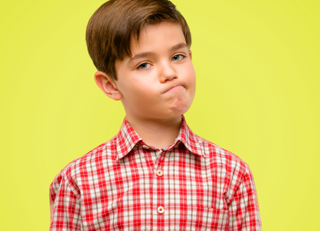 Handsome toddler child with green eyes making funny face fooling over yellow background