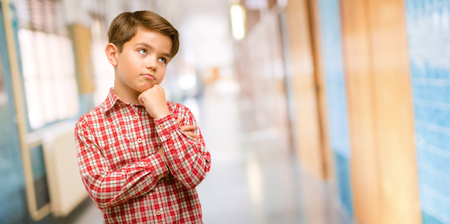 Handsome toddler child with green eyes thinking and looking up expressing doubt and wonder at school corridor Stock Photo