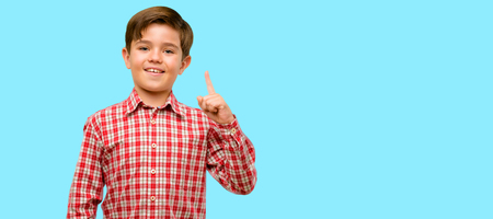Handsome toddler child with green eyes happy and surprised cheering expressing wow gesture pointing up over blue background Stock Photo