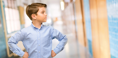Handsome toddler child with green eyes side view portrait at school corridor