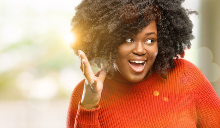 Beautiful african woman happy and surprised cheering expressing wow gesture, outdoor Stock Photo