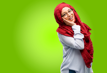 Young arab woman wearing hijab happy and surprised cheering expressing wow gesture