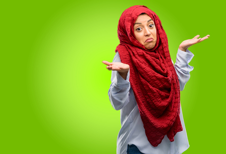 Young arab woman wearing hijab doubt expression, confuse and wonder concept, uncertain future shrugging shoulders