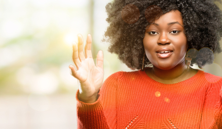 Beautiful african woman confident and happy with a big natural smile welcome gesture, outdoor