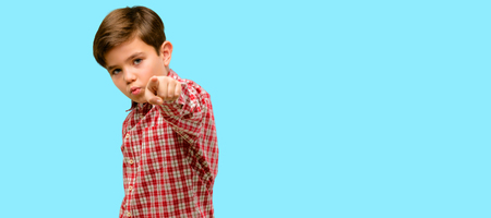 Handsome toddler child with green eyes pointing to the front with finger over blue background