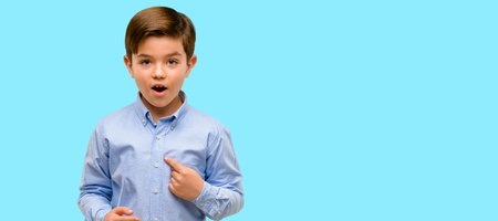Handsome toddler child with green eyes happy and surprised cheering expressing wow gesture, pointing with finger over blue background