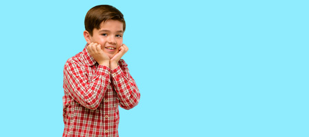 Handsome toddler child with green eyes happy and surprised cheering expressing wow gesture over blue background