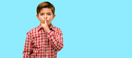 Handsome toddler child with green eyes with index finger on lips, ask to be quiet. Silence and secret concept over blue background