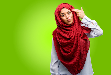 Young arab woman wearing hijab unhappy making suicide gesture, tired of everything. Shoots with his hand imitating gun, upset Stock Photo