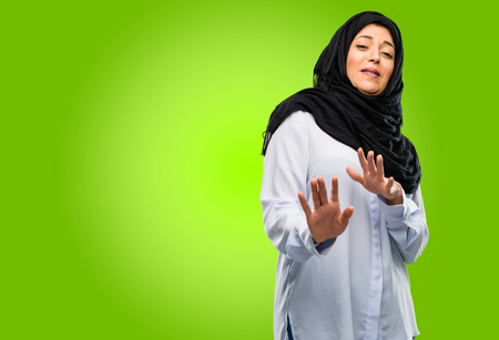 Young arab woman wearing hijab disgusted and angry, keeping hands in stop gesture, as a defense, shouting Stock Photo