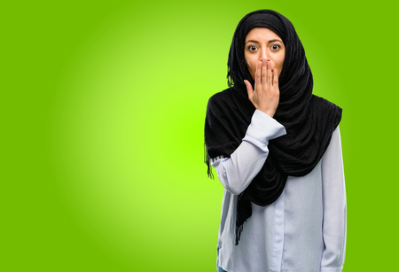 Young arab woman wearing hijab covers mouth in shock, looks shy, expressing silence and mistake concepts, scared 版權商用圖片