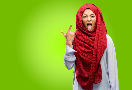 Young arab woman wearing hijab making rock symbol with hands, shouting and celebrating with tongue out