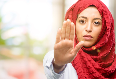 Young arab woman wearing hijab annoyed with bad attitude making stop sign with hand, saying no, expressing security, defense or restriction, maybe pushing
