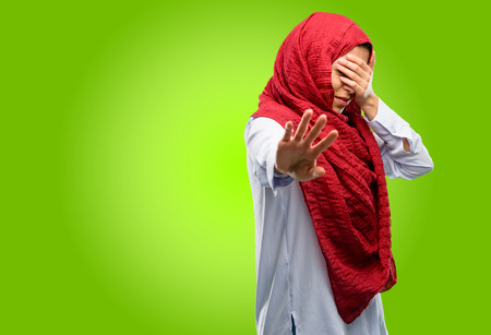 Young arab woman wearing hijab stressful and shy keeping hand on head, tired and frustrated