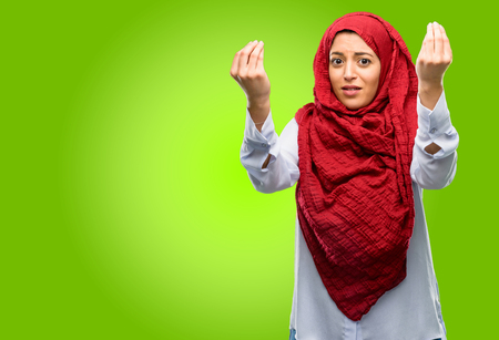Young arab woman wearing hijab angry gesturing typical italian gesture with hand, looking to camera