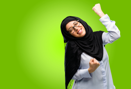 Young arab woman wearing hijab happy and excited celebrating victory expressing big success, power, energy and positive emotions. Celebrates new job joyful Banque d'images - 104012088