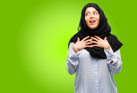 Young arab woman wearing hijab having charming smile holding hands on heart wanting to show love and sympathy