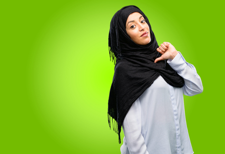 Young arab woman wearing hijab proud, excited and arrogant, pointing with victory face Stock Photo