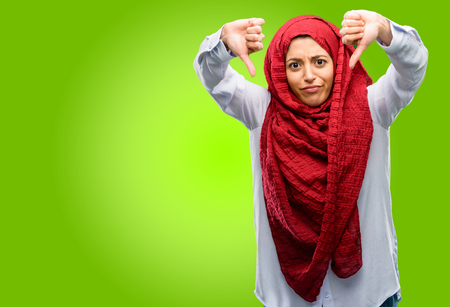 Young arab woman wearing hijab showing thumbs down unhappy sign of dislike, negative expression and disapproval Stock Photo