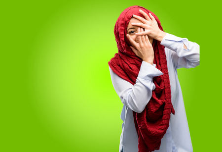 Young arab woman wearing hijab smiling having shy look peeking through her fingers, covering face with hands looking confusedly broadly Stock Photo