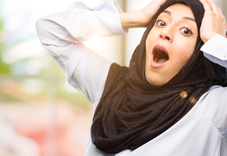 Young arab woman wearing hijab stressful keeping hands on head, terrified in panic, shouting