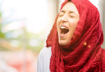 Young arab woman wearing hijab stressful, terrified in panic, shouting exasperated and frustrated. Unpleasant gesture. Annoying work drives me crazy