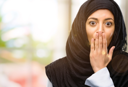 Young arab woman wearing hijab covers mouth in shock, looks shy, expressing silence and mistake concepts, scared Banco de Imagens