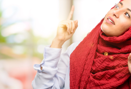 Young arab woman wearing hijab happy and surprised cheering pointing up Stock Photo
