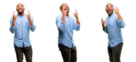 African american man with beard happy and surprised cheering expressing wow gesture pointing up