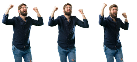 Young man with beard happy and excited celebrating victory expressing big success, power, energy and positive emotions. Celebrates new job joyful isolated over white background